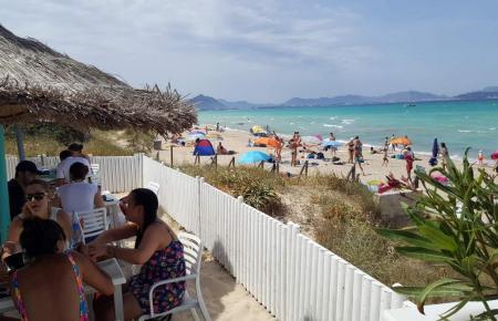 Touristen an einem Strand auf Mallorca.