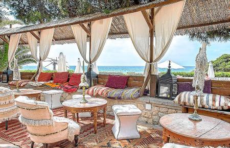 Weitläufige Terrasse mit viel Platz und dahinter glitzert das Meer.