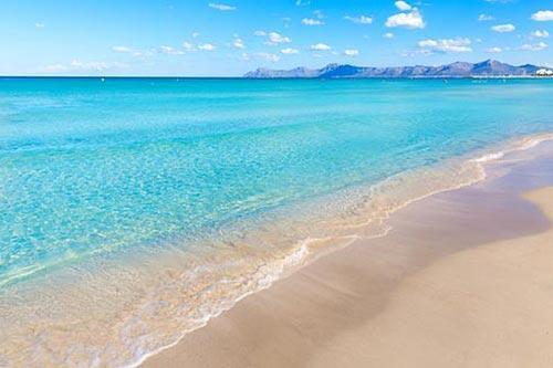 Am Strand von Can Picafort strahlt das türkisblaue Meer.