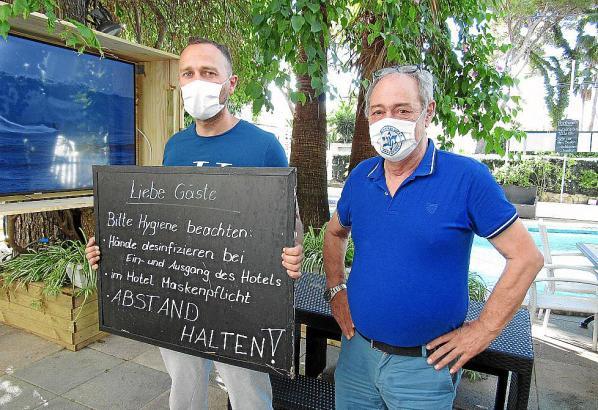 Kevin (l.) und sein Vater Bernd Hartmann vor dem Hotelpool. Am Hauseingang werden die Gäste auf die aktuell gültigen Corona-Regeln hingewiesen.