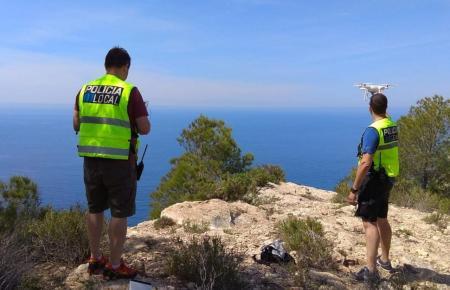 Polizisten mit einer Drohne am Ort des Vorfalls.