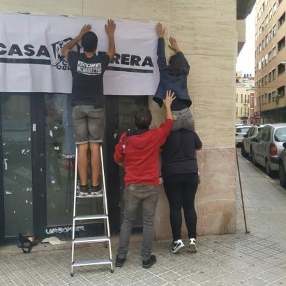 Die Besetzer hängen ein Plakat an den Eingang.