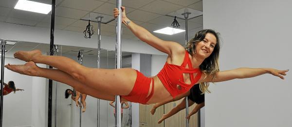 """Scheinbar schwerelos """"hängt"""" Poletänzerin Alessandra Petragnani an der Stange. In Wirklichkeit ist es fast Hochleistungssport."""