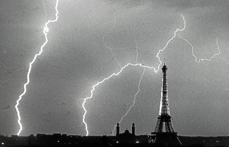 Die Elektrizität der Natur taucht den Eiffelturm, das Wahrzeichen von Paris, in ein gespenstisches Licht.