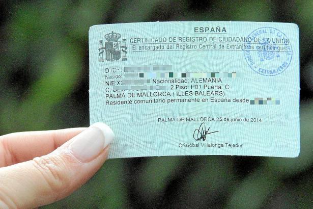 Eine Residentin hält nach erfolgreichem Prozedere ihre grüne Karte in der Hand.