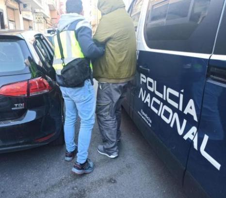 Einer der Festgenommen wird von einem Beamten der spanischen Nationalpolizei abgeführt.