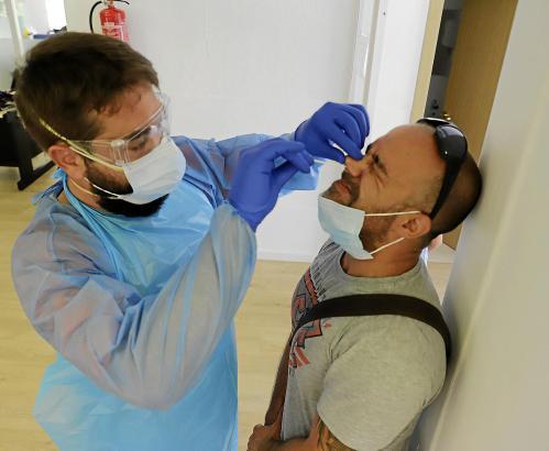 Der Mitarbeiter des balearischen Gesundheitssystems führt einen PCR-Test durch. Dabei wird ein dünnes Wattestäbchen tief in die Nasenhöhle eingeführt.