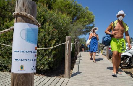Maskenträger an einem Küstenabschnitt.
