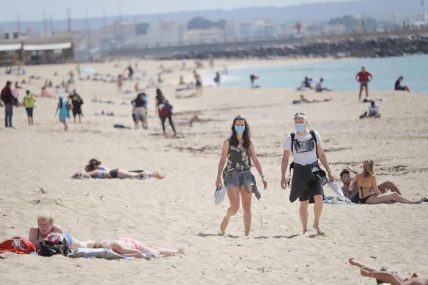 Maskenträger an einem spanischen Strand.