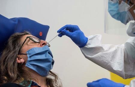 Bei einer Patientin wird ein Corona-Nasenabstrich durchgeführt.