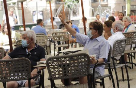 Maskenträger auf einer Restaurantterrasse auf Mallorca.