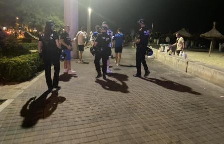 Polizisten lösen eine Versammlung an der Playa de Palma auf.