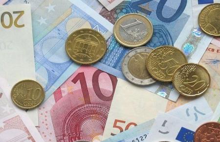 Der Deutsche schätzt Scheine und Münzen in der Hand.