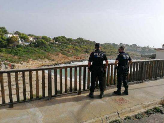 Zwei Polizeibeamten während der Ermittlungen am Strand von Cala Mendia bei gehisster roter Flagge.