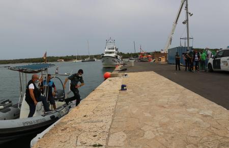 Polizisten und andere Helfer am Montag im Hafen von Portocolom, wohin die Toten gebracht wurden.