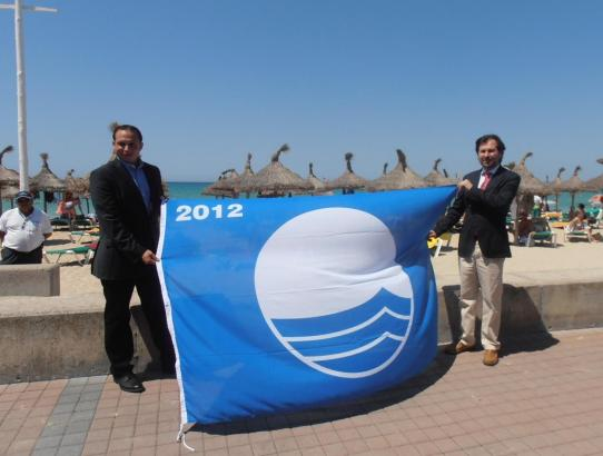 Palmas Umweltdezernent Andreu Garau und Stadtrat Joan Pau Reus, posieren mit der blauen Flagge, bevor sie am Mast gehisst w