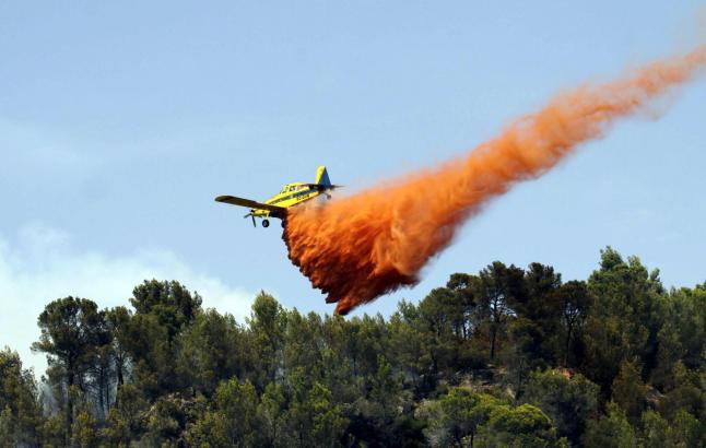 Ein Löschflugzeug wirft eine Ladung Flammschutzmittel über den Wäldern bei Son Vida ab.