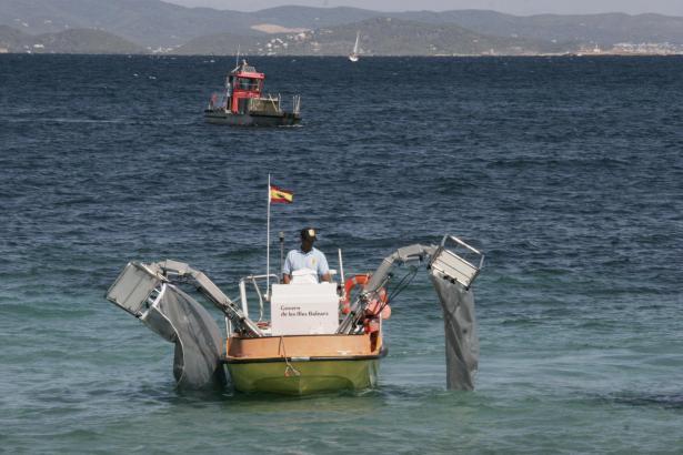 Eines der Müllboote im Einsatz. Fangkörbe fischen treibenden Abfall aus dem Wasser.