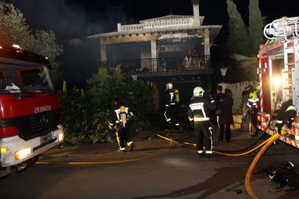 Feuerwehrmänner löschen den Brand in dem Chalet.