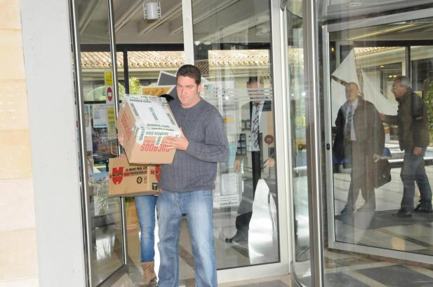 Ein Polizeibeamter in Zivil trägt sichergestellte Dokumente aus dem Rathaus von Calvià.