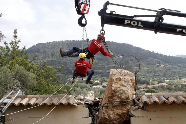 Feuerwehrmänner legen dem Felsbrocken eine Stahlschlinge um.