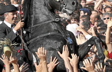 Ein gefährlicher Spaß: Inmitten der Menschenmenge bringt der Reiter das Pferd zum Aufbäumen - und viele Hände versuchen es hochz