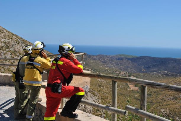 Feuerwehrleute blicken nach dem Einsatz auf die verbrannte Hügelkette im Nordosten Mallorcas.