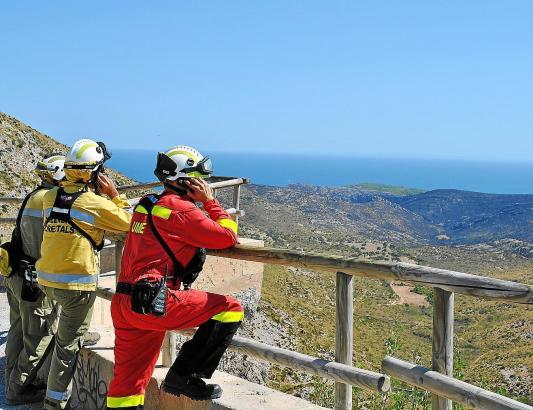 (Wieder) entspannte Feuerwehrleute blicken auf die verbrannte Hügelkette.