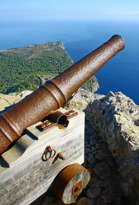 Auf dem Penya des Migdia steht eine alte Kanone. Im Hintergrund: Das Cap de Pinar, bis heute Militärgelände.