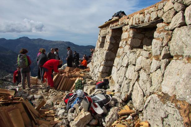 Freiwillige Helfer beim Wiederaufbau der alten Wanderhütte.