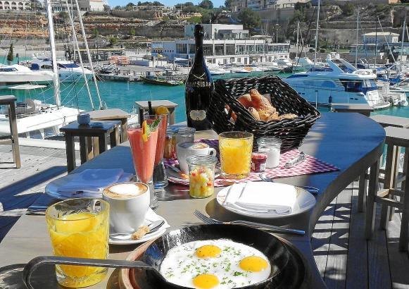 """Lecker frühstücken und auf Boote schauen - das kann man im """"Sansibar Wine"""" in Port Adriano auf Mallorca."""
