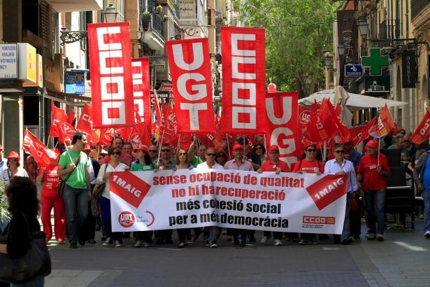 Mit roten Gewerkschaftsfahnen für gerechtere Arbeitsbedingungen.