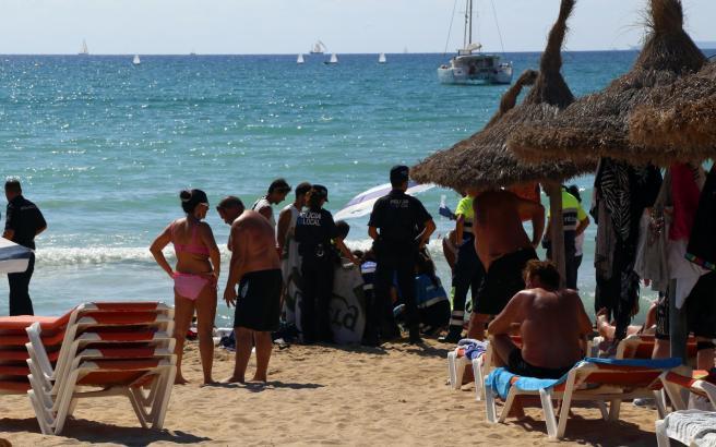 Wiederbelebung an der Playa: Beamte der Polizei schirmen die Rettungsaktion ab.