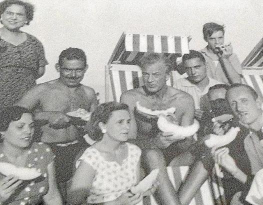 Gary Cooper im Kreise von Fischern und ihren Frauen beim Melonen-Essen am Strand.