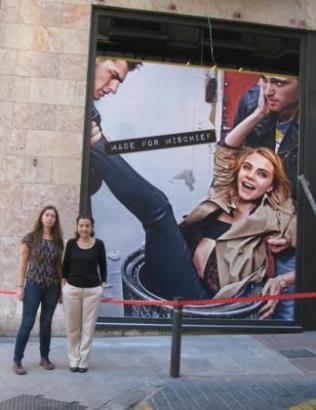 Zwei Mitglieder der Oppositionspartei Més vor dem umstrittenen Werbeplakat.