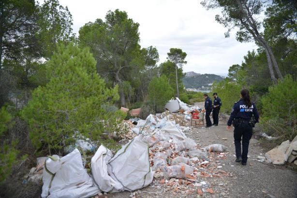 Polizebeamte untersuchen den achtlos weggeworfenen Müll und Bauschutt.