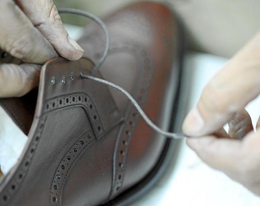 Am Ende der Fertigung zieht der Schuhmacher den Schnürsenkel in sein Handwerk ein.