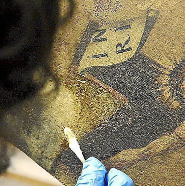 Mit einem Wattestäbchen werden der Christusfigur behutsam die Verunreinigungen entfernt.
