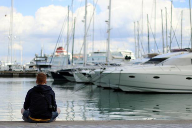 Ein junger Mann genießt den Ausblick am Hafen von Palma.