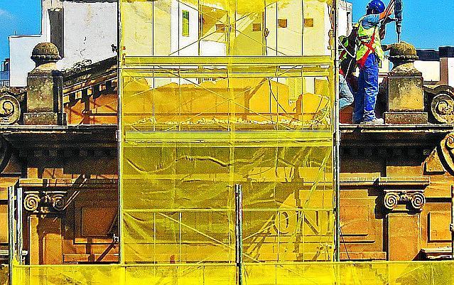 Arbeiter entfernten den Schriftzug des historischen Gebäudes