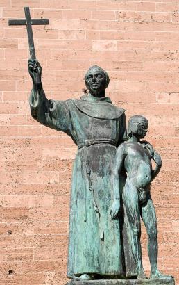Die Bronzestatue vor der Basilika Sant Francesc in Palma zeigt Junípero Serra als Missionar mit einem Indianerjungen.
