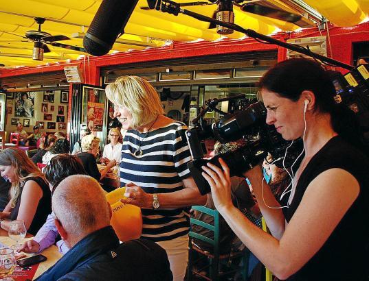 Kamerafrau Eva Gühne filmt, wie Auswanderin Andrea Lang im Kultbistro in Santa Ponça Spenden für einen Obdachlosen sammelt