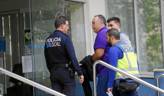Einer der tatverdächtigen Polizisten wird von Ermittlern zur Durchsuchung seines Arbeitsplatzes in der Polizeiwache Sant Ferran