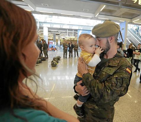Ein Soldat verabschiedet sich von Kind und Frau an Palmas Flughafen