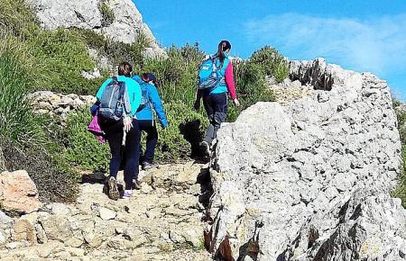 Wanderer steigen bei Ses Voltes d'En Galileu hinauf.
