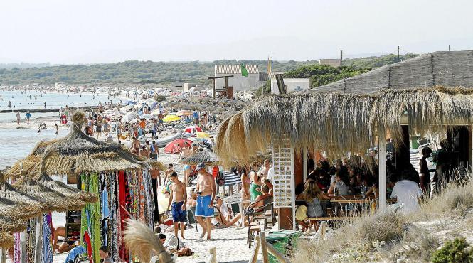 An dem geschützten Naturstrand Es Trenc drängen sich im Sommer mehrere Verkaufsstände neben Sonnenschirmen und Liegen