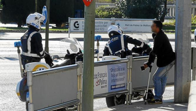 Polizeibeamte kontrollieren einen Bettler an einer Ampel in Palma.