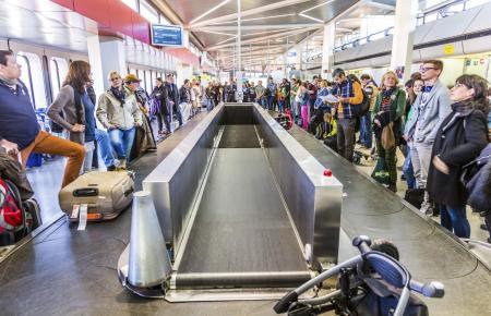 Wo ist mein Koffer? Wartende am Gepäckband eines Flughafens.