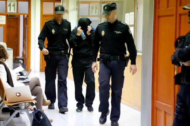 Einer der beschuldigten Polizisten nach der Festnahme im Gang des Gerichtsgebäudes in Palma.