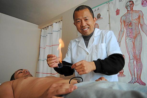 Bis die Nadelspitze glüht: Der chinesische Heiler Yan Tao Pan in seinem Behandlungsraum an der Playa de Palma.